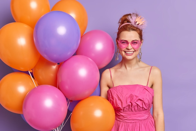 Positive happy woman at valentines day party with multicolored balloons dressed in retro style clothes and accessories poses
