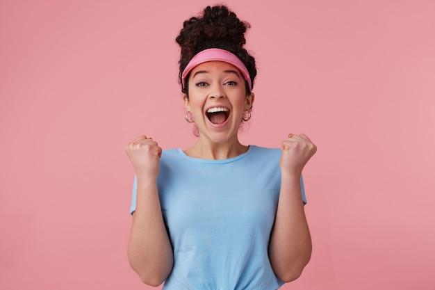 暗い巻き毛のお団子を持つポジティブで幸せな女性。ピンクのバイザー、イヤリング、青いtシャツを着ています。補っている。興奮して拳を握り締める