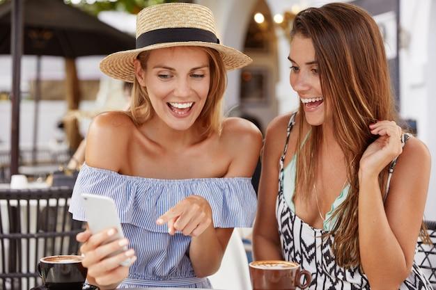 Le donne felici positive hanno vacanze estive, felici di vedere un'offerta speciale per i turisti sul sito internet, puntano con un'espressione gioiosa sullo schermo dello smartphone. persone, tempo libero, concetto di tecnologia