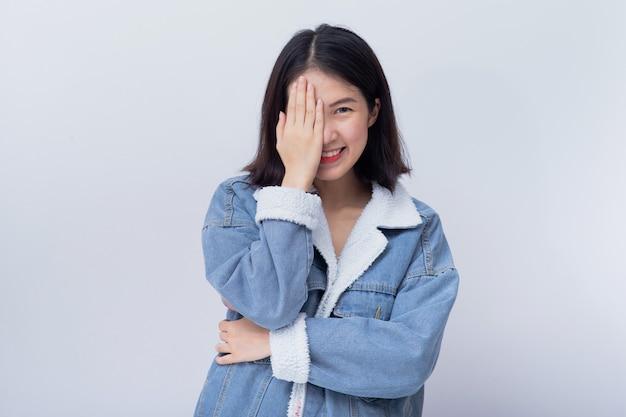 Положительная счастливая молодая азиатская женщина покрывая один глаз