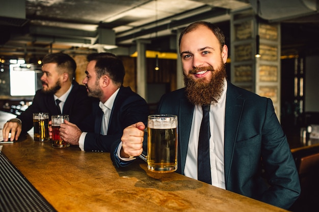 Positive and happy young businessman sit at bar counter. he smiles on camera. guy hold beer mug. other two office workers sit behind.