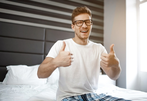 Positive happy young man on bed in morning. he look on camera and show big thumbs up. male model wear pajama and glasses.