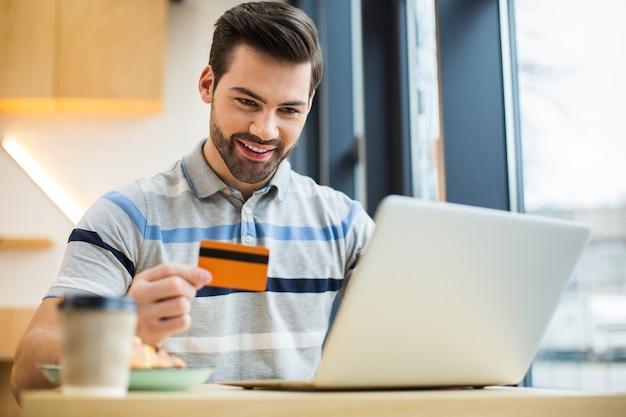 Позитивный счастливый молодой человек, держащий кредитную карту и улыбающийся, делая онлайн-платеж