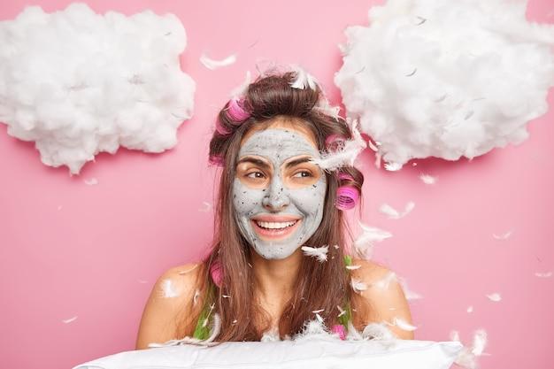 베개 싸움이 머리 롤러를 착용 한 후 긍정적 인 행복 한 젊은 여자가 쾌활한 분위기를 가지고 있습니다. 뷰티 페이스 마스크 미소는 분홍색 벽 위에 고립 된 공기에서 깃털을 날리며 즐겁게 포즈를 취합니다.
