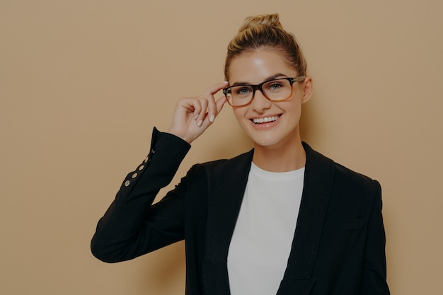 Positive happy young woman touching rim of glasses and looking through them, smiling female student touching spectacles while looking at camera with smile, isolated over beige wall with copy space