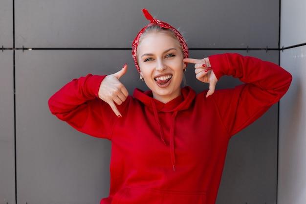 夏の日の灰色の建物の近くの街でポーズをとって流行のバンダナとスタイリッシュな赤いスウェットシャツでかわいい笑顔でポジティブな幸せな若い女性