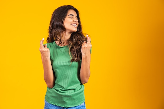 Positive and happy young woman with crossed fingers wishing luck.