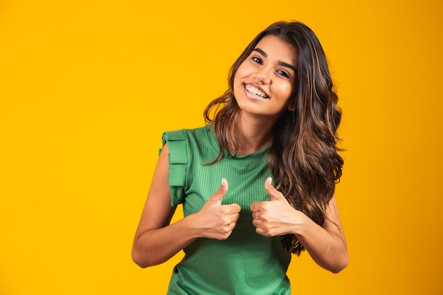Positive and happy young woman with thumb up.