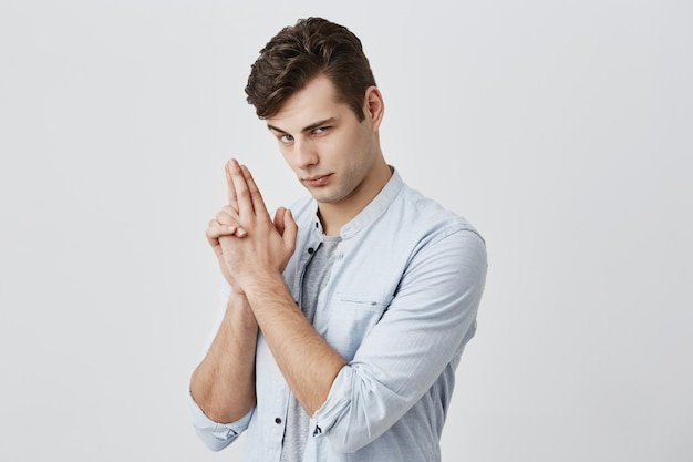 Positive having fun caucasian male with dark hair and blue eyes, raised hie eyebrow, making faces, seriously looking , gesturing pretending to have gun. fun and youth concept