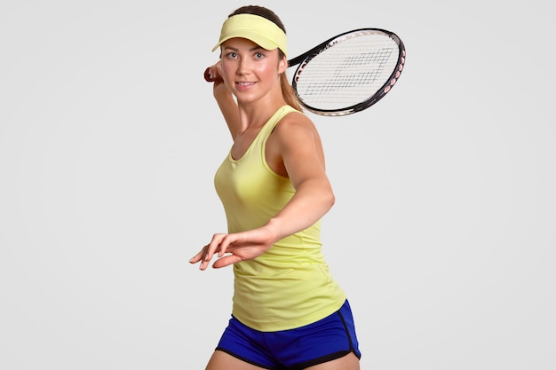 Positive healthy active sporty woman warms up before match, dressed in casual outfit, ready to hit ball with raquet, poses against white studio wall. people, motivation, activity concept