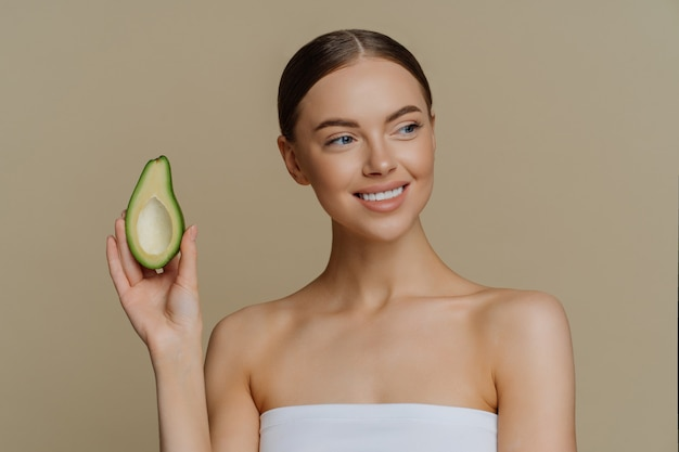 Positive healthy pleased woman looks tenderly aside smiles gently holds half of avocado