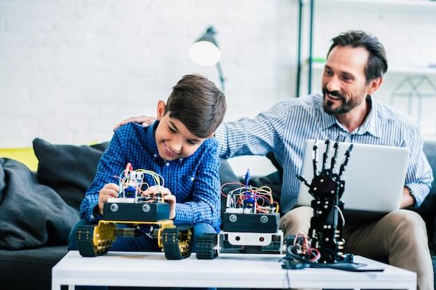 ロボット工学プロジェクトに取り組んでいる彼の息子を称賛する前向きで親切な父親