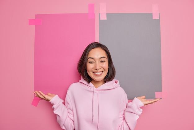 La donna asiatica esitante positiva allarga le pose delle palme al coperto contro due fogli di carta intonacati sulla parete rosa indossa una felpa con cappuccio suggerisce di utilizzare lo spazio della copia ha un'espressione felice