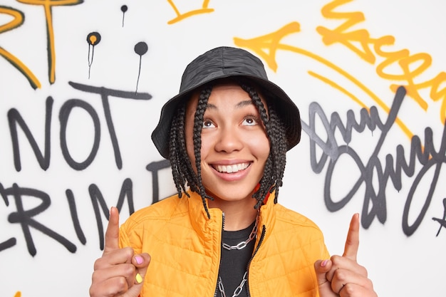 Positive hipster girl with braids smiles broadly points index fingers overhead dressed in fashionable clothes demonstrates something against graffiti wall belongs to youth subculture