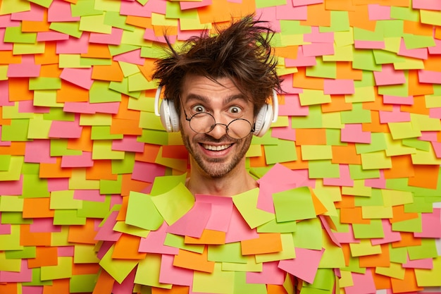Positive hipster wears round spectacles, enjoys listening audio track in stereo headphones, chuckles from joy, has messy hairstyle, sticks out head from paper wall with colorful sticky notes