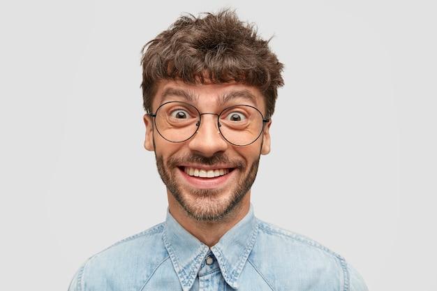 Hipster positivo con barba scura, ha un sorriso gentile e sincero, guarda con gli occhi pieni di felicità