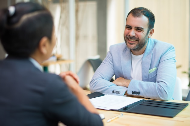 Positive hispanic businessman listening to colleague