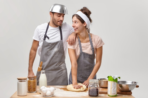 Positive housewife gives culinary master class for husband, shows how to make and knead dough, prepare breakfast together in cozy home, make cookies, wear aprons, spend free time at kitchen.