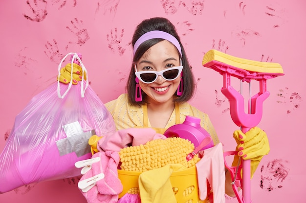 Positive housewife happy to finish housework cares of cleanliness and hygiene holds mop and polythene trash bag wears sunglasses stands untidy after washing or laundering isolated over pink wall