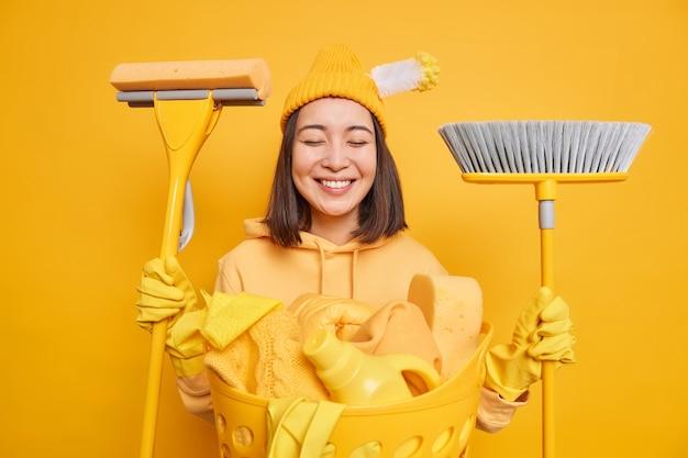 掃除用品でポーズをとるポジティブな主婦は帽子にブラシが刺さっていますゴム製の保護手袋を着用していますカジュアルなパーカーは家事をし、洗濯物は黄色の背景の上に隔離された汚れた部屋を掃除します