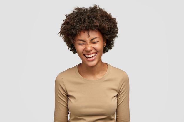 Концепция положительных человеческих эмоций. счастливая кудрявая молодая афро-американская женщина с радостным выражением лица, хихикает и смеется над чем-то смешным, прищуривается от счастья, изолирована на белой стене