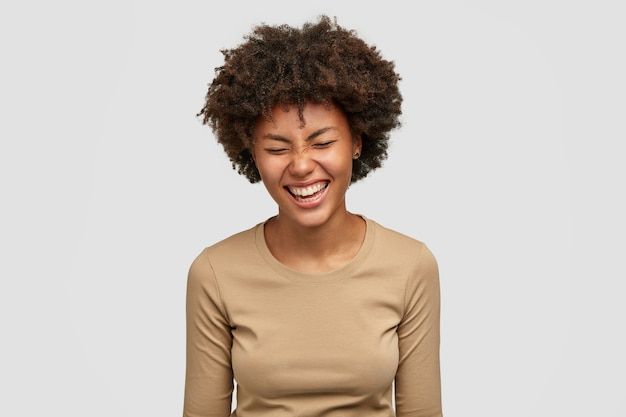 Positive human emotions concept. happy curly young african american woman with glad expression, giggles and laughs at something funny, squints face from happiness, isolated over white wall