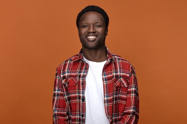Положительные человеческие эмоции, чувства и восприятие жизни. изолированные изображение красивый молодой темнокожий мужчина, одетый в стильную клетчатую рубашку, наслаждаясь досугом, получая хорошие новости, счастливо улыбаясь