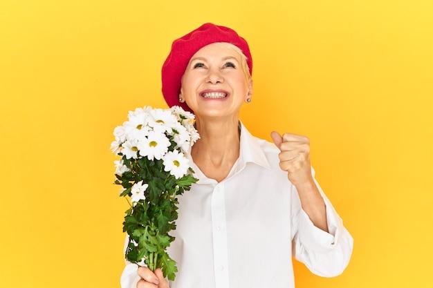 ポジティブな人間の感情、感情、反応。エレガントなヘッドウェアと白いシャツを着て、見上げて笑って、デイジーを持って、拳を握りしめ、成功に興奮している感情的な恍惚とした引退した女性