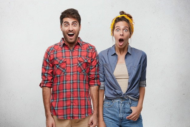 Positive human emotions, feelings, attitude and reaction concept. portrait of surprised young bearded man in red plaid shirt and woman with headband posing