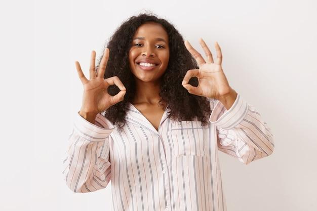 Emozioni umane positive, sentimenti ed espressioni facciali. attraente ragazza africana gioiosa con acconciatura voluminosa e ampio sorriso radioso, mostrando il gesto giusto, collegando il pollice e l'indice