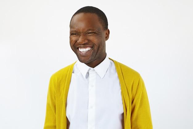 Emozioni umane positive, sentimenti, gioia e concetto di felicità. colpo di studio isolato di bel ragazzo afroamericano emotivo giovane con denti dritti perfetti sorridendo felicemente, ridendo di scherzo