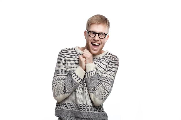 Emozioni umane positive, sentimenti, reazione e atteggiamento. immagine di uno studente maschio estatico divertente con gli occhiali, che tiene i pugni chiusi sul petto e sorride ampiamente, eccitato dai risultati degli esami