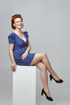 Positive human emotions, feelings and reaction. picture of happy cheerful beautiful young woman wearing low neck retro dress sitting on white object and laughing, being in good mood