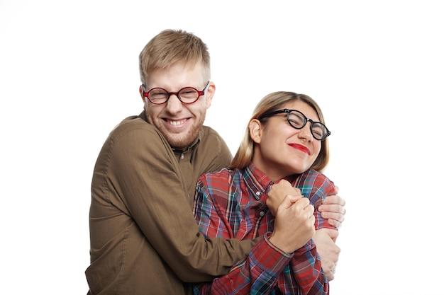 ポジティブな人間の感情、幸福と喜びの概念。楽しんでいる眼鏡の陽気な若いカップルの水平方向のショット:タイトな笑顔の女性を保持している変な顔のひげを生やした男