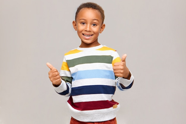 긍정적 인 인간의 감정, 반응 및 감정. 멀티 컬러 점퍼에 감정적 인 행복 어두운 피부 소년 제스처 엄지 손가락을 만들고, 동의, 승인을 표현하고, 자신이 좋아하고, 광범위하게 웃고 있습니다.