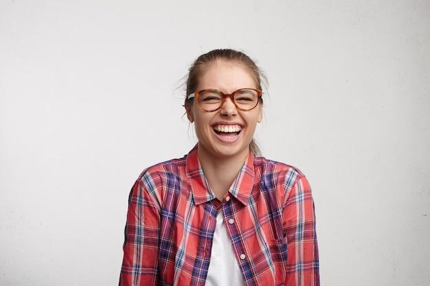 肯定的な人間の感情。良いジョークで大声で笑いながら室内で友達と楽しんでいる間目を閉じて眼鏡をかけてこぼれるような笑顔でリラックスした屈託のない若い女性のスタジオポートレート