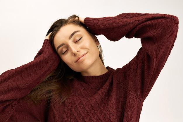 긍정적 인 인간의 표정과 감정. 니트 스웨터에 매력적인 젊은 백인 여성의 고립 된 총은 즐거움으로 눈을 감고, 머리를 마사지하고 즐겁게 웃고 있습니다.