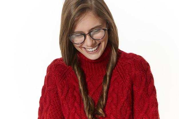 긍정적 인 인간의 표정, 감정, 감정 및 삶의 인식. 안경과 점퍼에 화려한 쾌활한 젊은 여자가 그녀의 머리를 돌리고 수줍은 귀여운 미소로 내려다보고