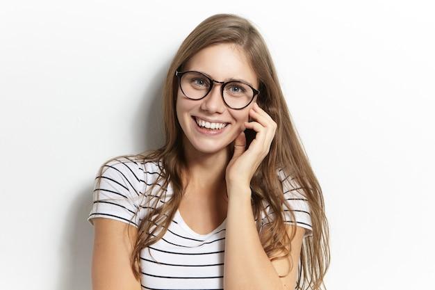 ポジティブな人間の表情、感情、感情、反応。冗談を笑いながら、広い陽気な笑顔で見ている眼鏡をかけている愛らしい美しいヨーロッパの女性のティーンエイジャー