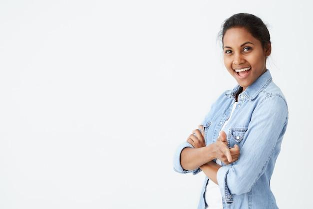긍정적 인 인간의 표정, 감정, 감정, 반응 및 태도. 매력적인 아프리카 계 미국인 여성 머리 롤빵, teet 함께 웃고. 보고 집게 손가락으로 가리키는