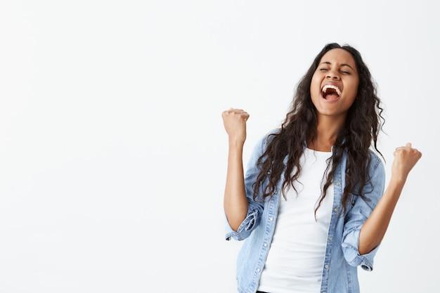 긍정적 인 인간의 얼굴 표정, 감정, 감정, 반응 및 태도. 느슨한 머리를 가진 매력적인 젊은 아프리카 계 미국인 여성은 놀라운 좋은 소식, 주먹 떨림, 외치며 놀랐습니다.