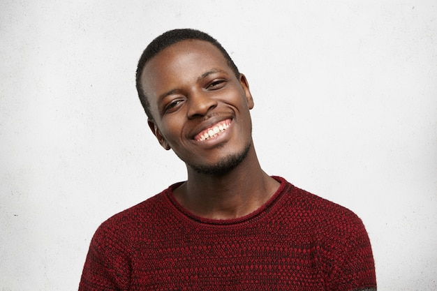Positive human facial expressions and emotions. headshot of handsome happy dark-skinned man dressed in casual sweater smiling kindly, showing his white teeth while pleased with compliment or good news