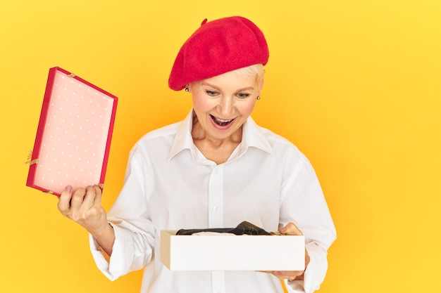 Positive human reactions and emotions. trendy emotional middle aged female in red bonnet exclaiming excitedly, having overjoyed astonished look, opening box with unexpected gift, keeping mouth opened