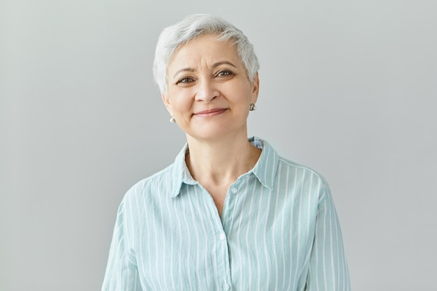 Positive human reactions, feelings and emotions. charming elegant middle aged sixty year old female with short gray hair  with pleased smile, her eyes full of happiness and joy