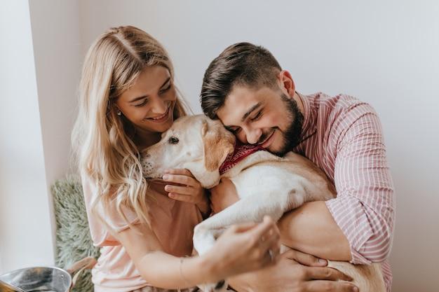 긍정적 인 남편과 아내가 강아지와 놀아요. 줄무늬 셔츠를 입은 남자는 부드러움으로 래브라도를 안아줍니다.
