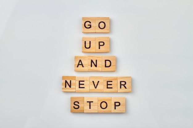 삶을 개선하기위한 긍정적 인 아이디어. 올라가서 절대 멈추지 마세요. 나무 큐브 흰색 배경에 고립입니다.