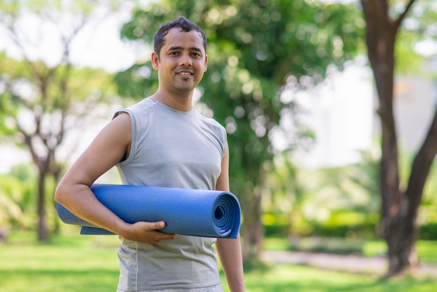 Positive indian guy with yoga mat getting ready for outdoor class.