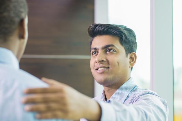 Positive indian professional congratulating colleague