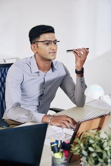 コンピューターで作業し、同僚のために音声メッセージを録音する眼鏡のポジティブなインドのプログラマー