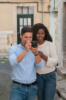 Positive interracial couple taking photos on camera in street